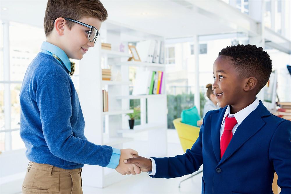Children entrepreneurs shaking hands