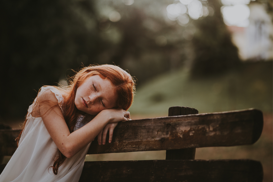 Young girl sleeping on bench in a park