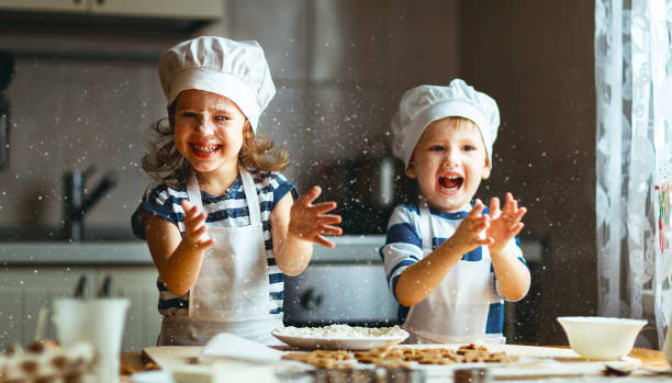 Two young children making cookies with dough in a kitchen
