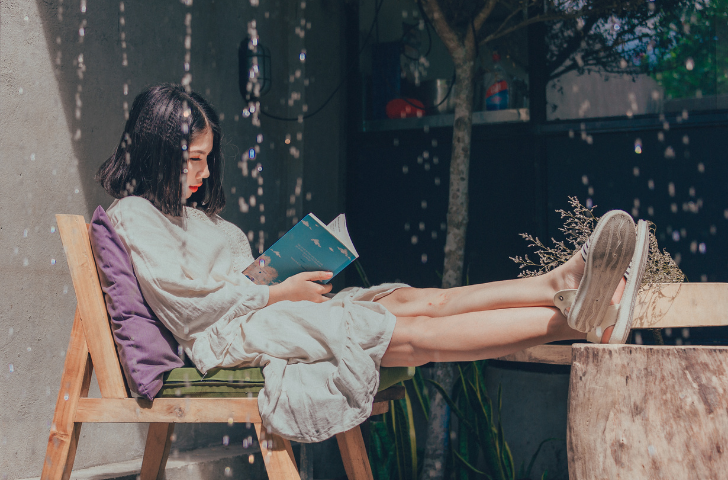 Young girl sitting outside reading