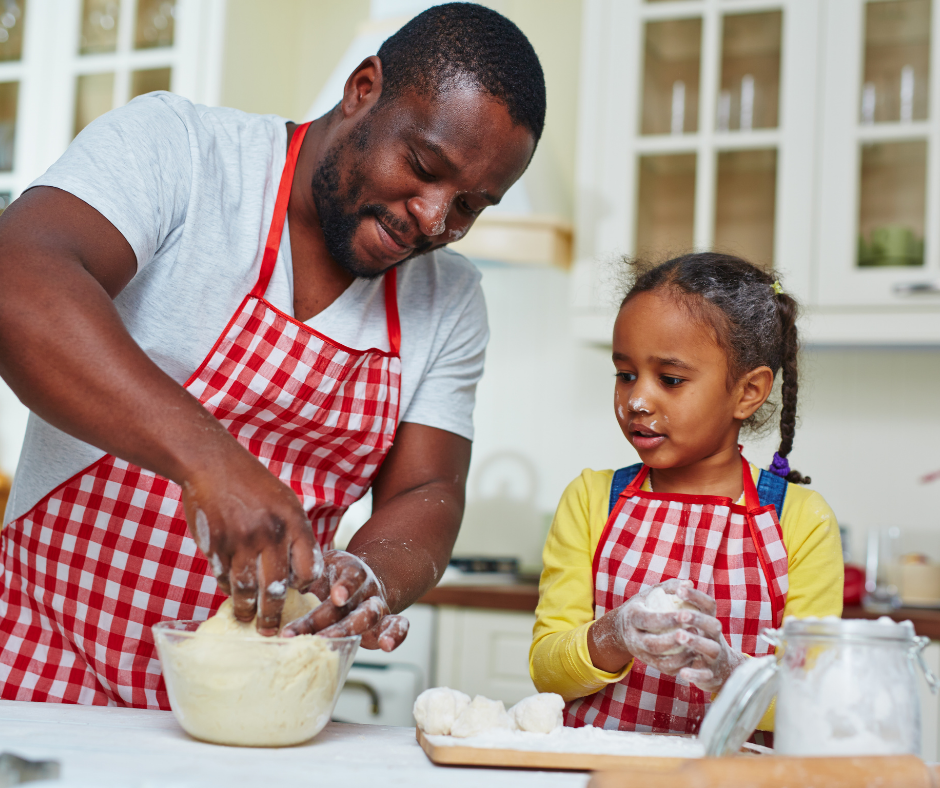 Father and young daughter rolling dough
