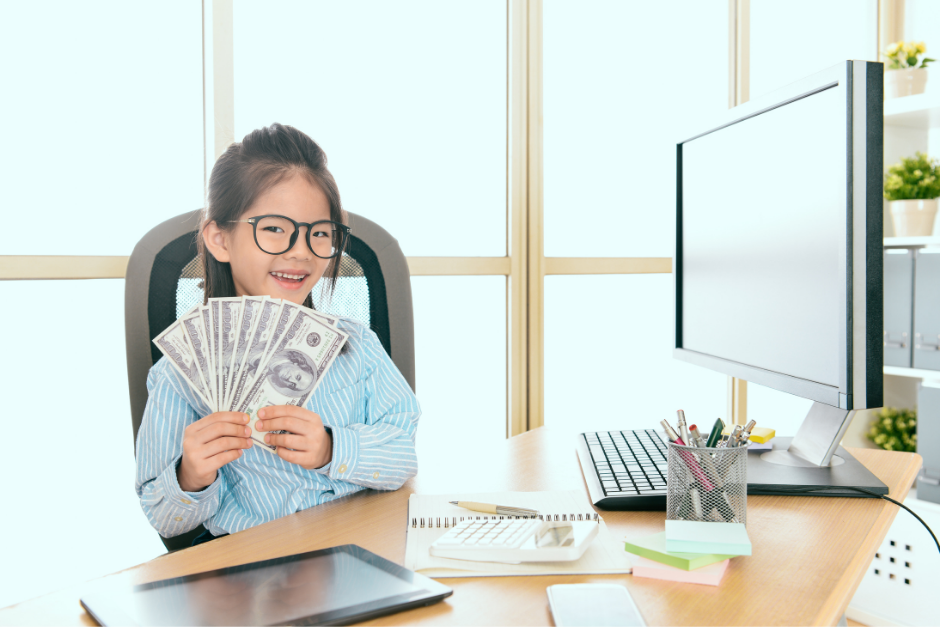 Young girl holding $100 bills at a computer desk and smiling