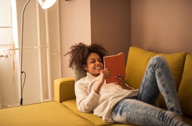 Woman lounging on a sofa while reading