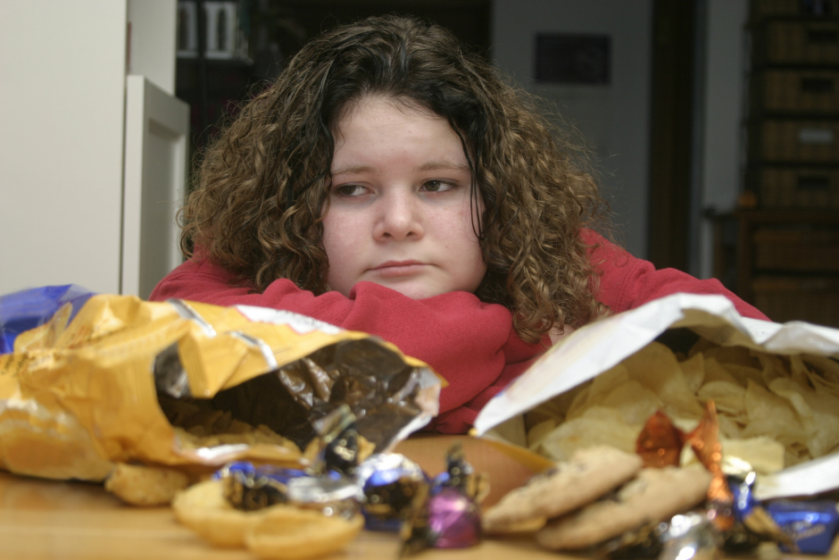 Young overweight girl looking stressed behind bags of chips
