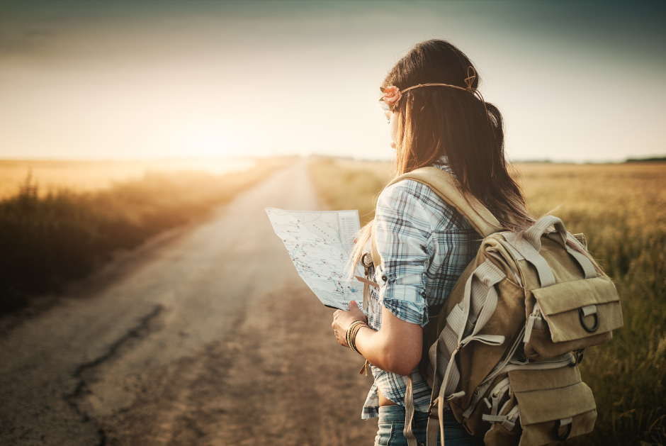 Young woman hiking and reading a map