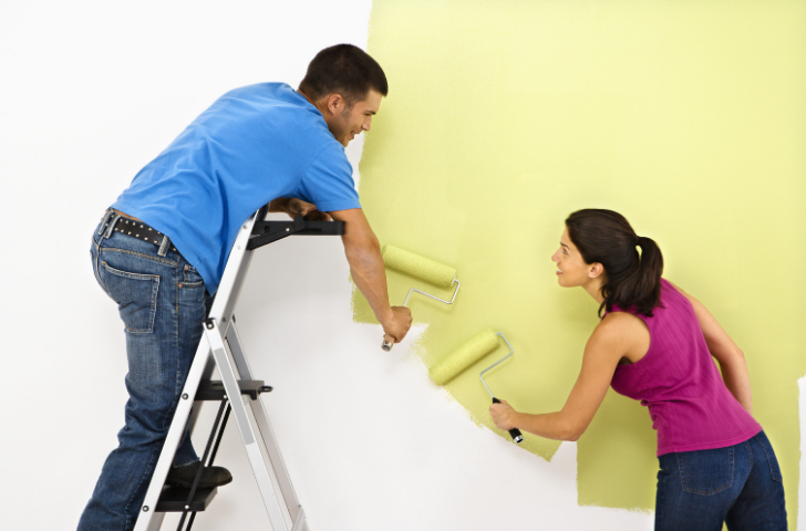 Couple painting a home wall