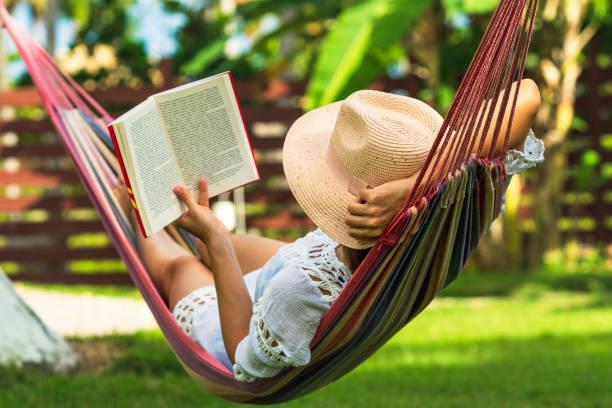 A woman reading a book on a hammock