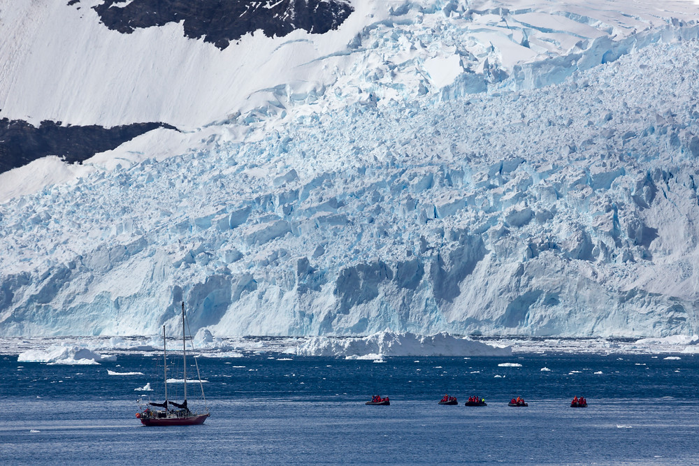 Small boats floating in front of large ice berg