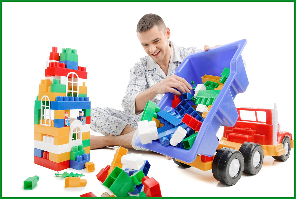 Adult make playing with LEGOs in pajamas