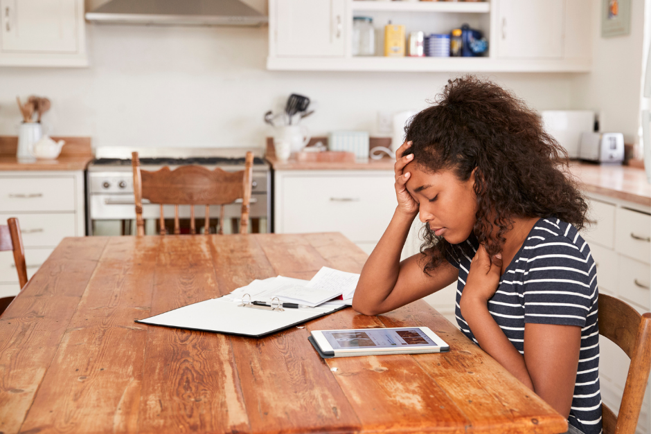Teenage girl sitting at kitchen table very stressed while looking at tablet