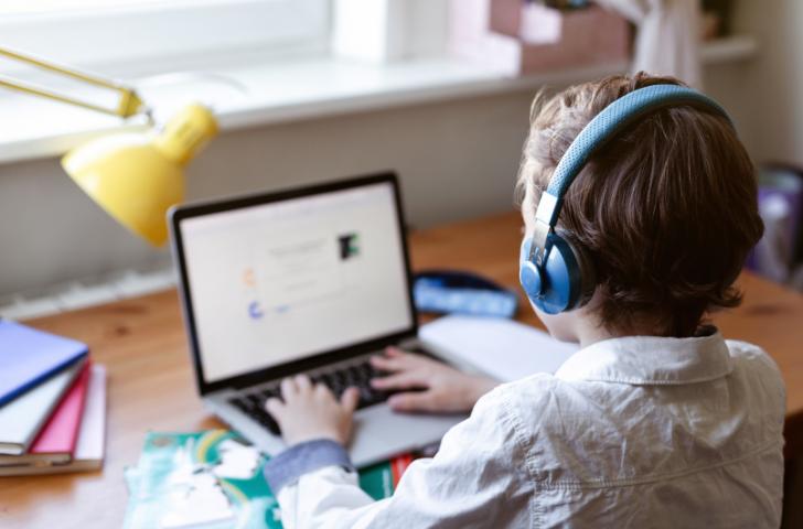 Little boy doing doing homework in laptop computer