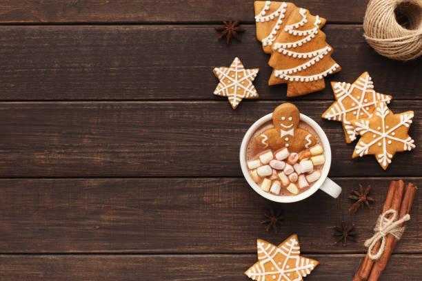 A gingerbread cookies sitting inside a mug of hot chocolate