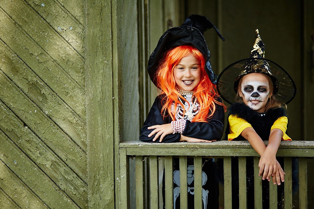Little girls in witch Halloween costumes