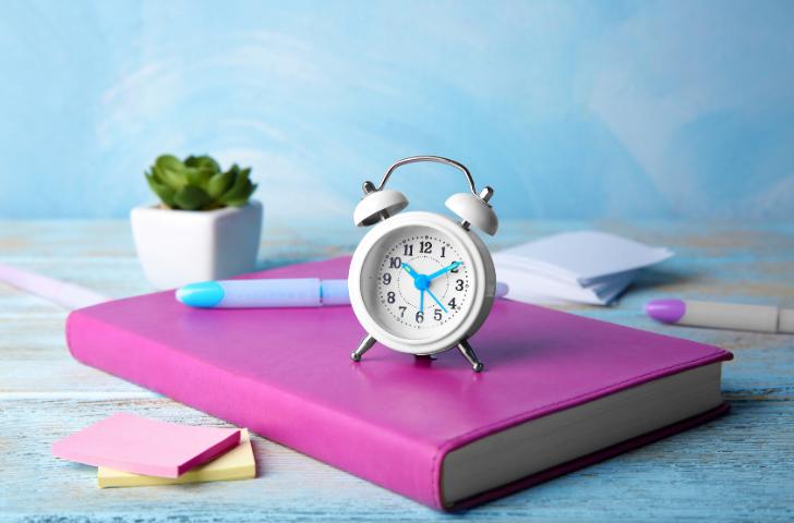 An analog alarm clock sitting atop a purple book.