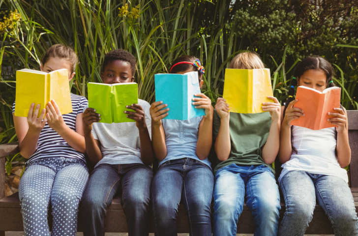 Children sitting together on a bench reading books