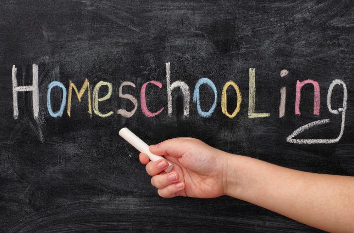 Homeschooling written on a chalk board by a child