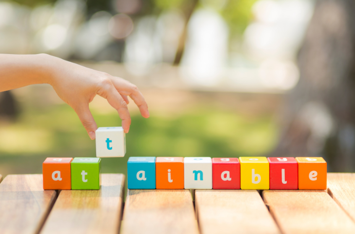 A child spelling the word attainable with letter blocks