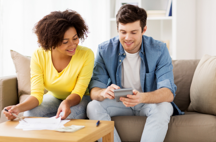 Young couple sitting on couch balancing budget
