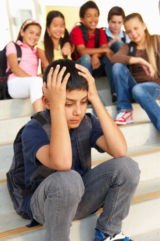Young boy sitting on school steps while being laughed at from kids behind him