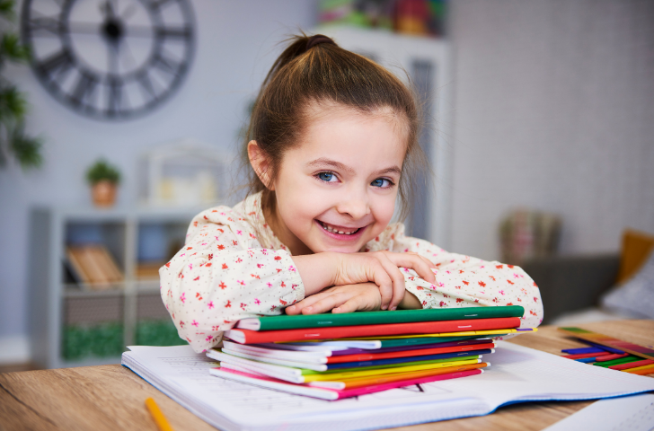 Little girl smiling while laying her head on school books