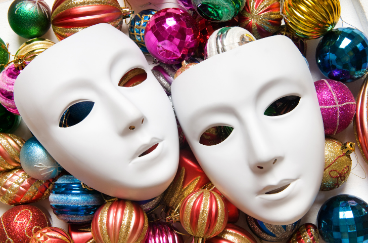 All White Mardi Gras masks sitting on colorful ornaments