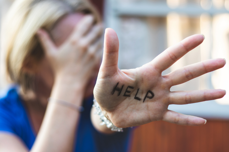 Woman with HEL P written on her left hand while hiding her face with her right hand