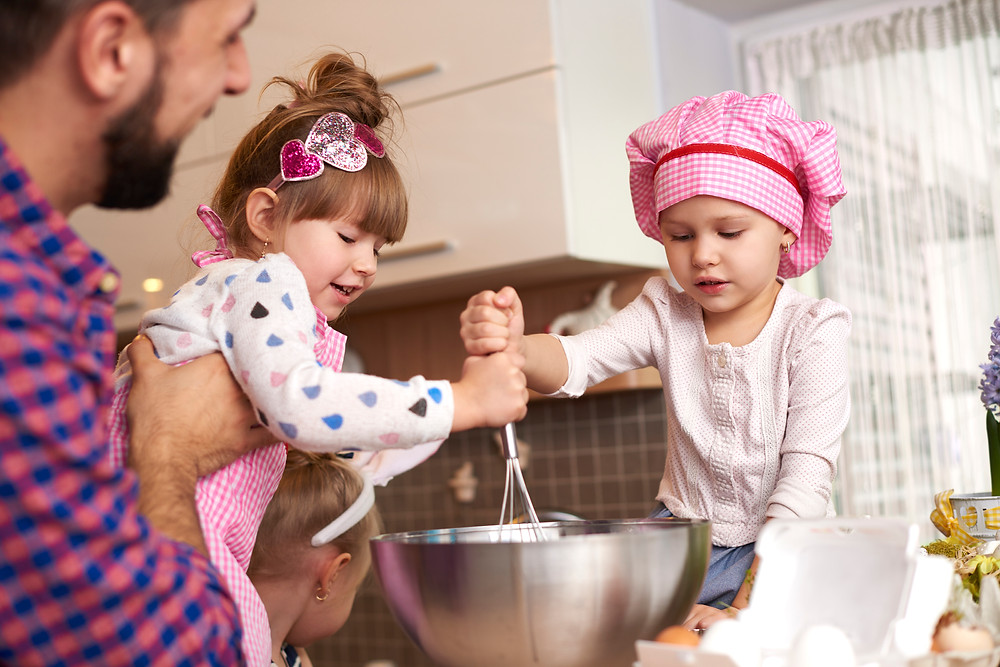 Father and three young daughters mixing ingredients in a bowl.