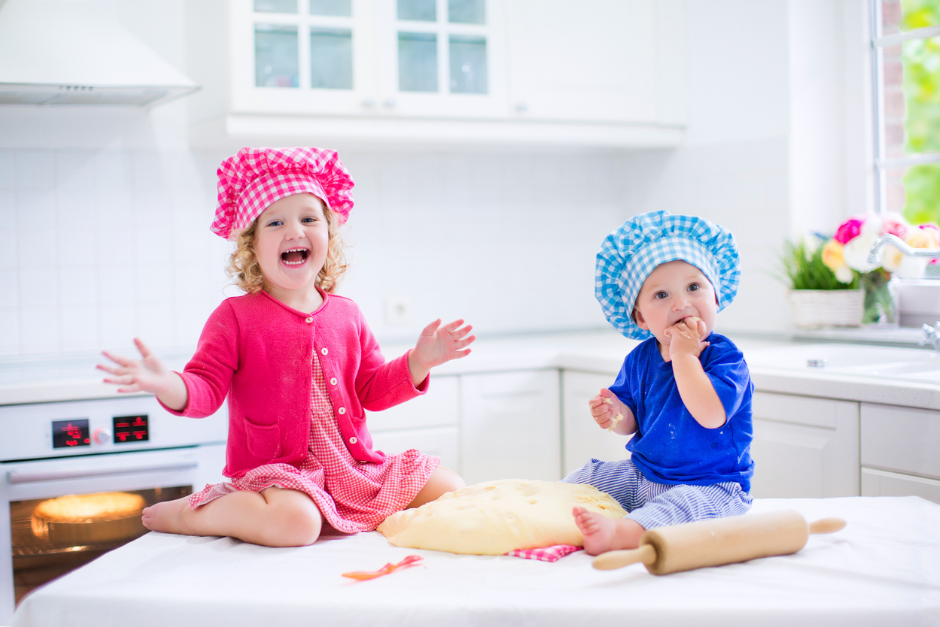 Two young children sitting on a kitchen counter rolling dough