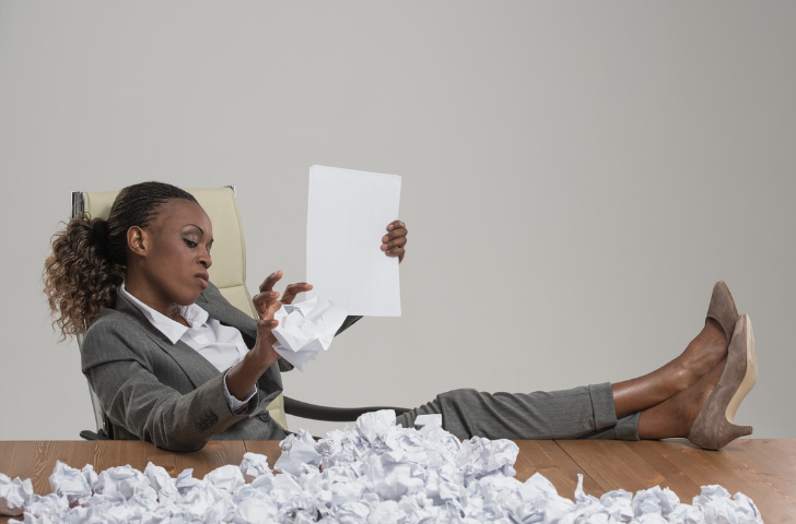 Woman sitting at desk with legs propped up and crumbling sheets of paper