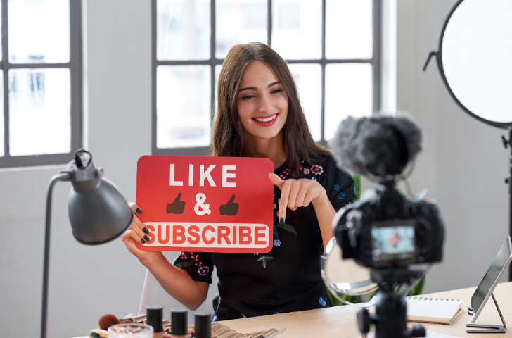 A woman being filmed requesting likes and subscribes