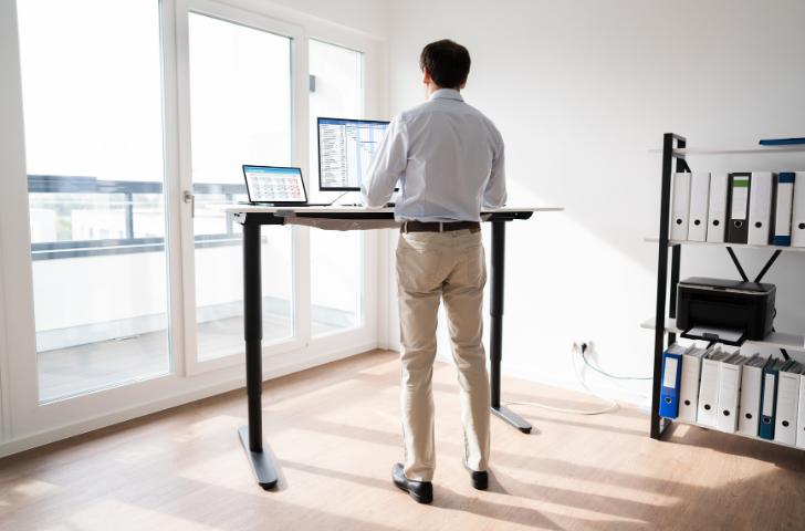 A man standing at a computer desk