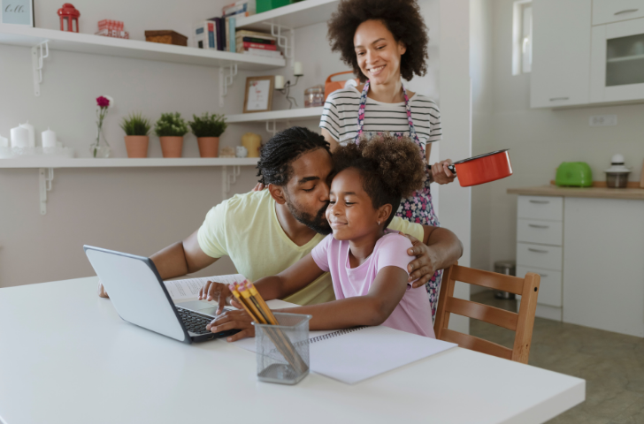 Mother and Father helping young daughter with homework on a laptop