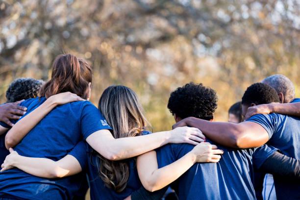 Group of diverse people huddling up together