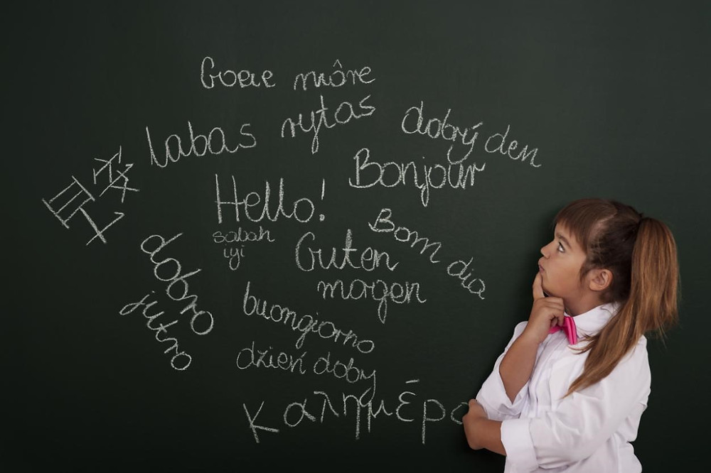 Little girl looking at hello in different languages