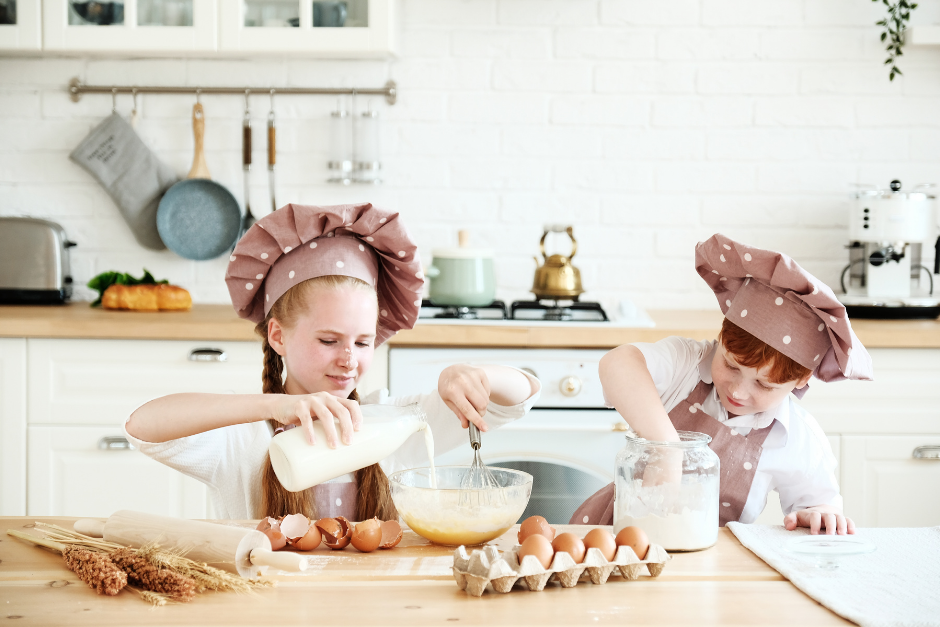 Two young girl chefs mixing flour in a bowl