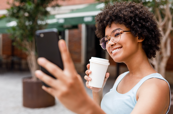 Woman taking a selfie while holding a cup of coffee