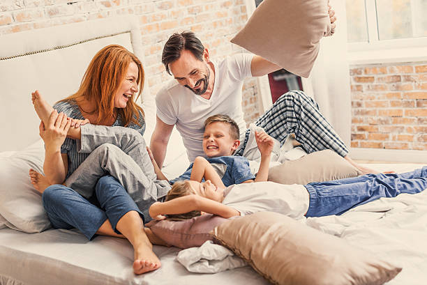 Mother - Father - Daughter - Son - Entire family laughing in a bed.