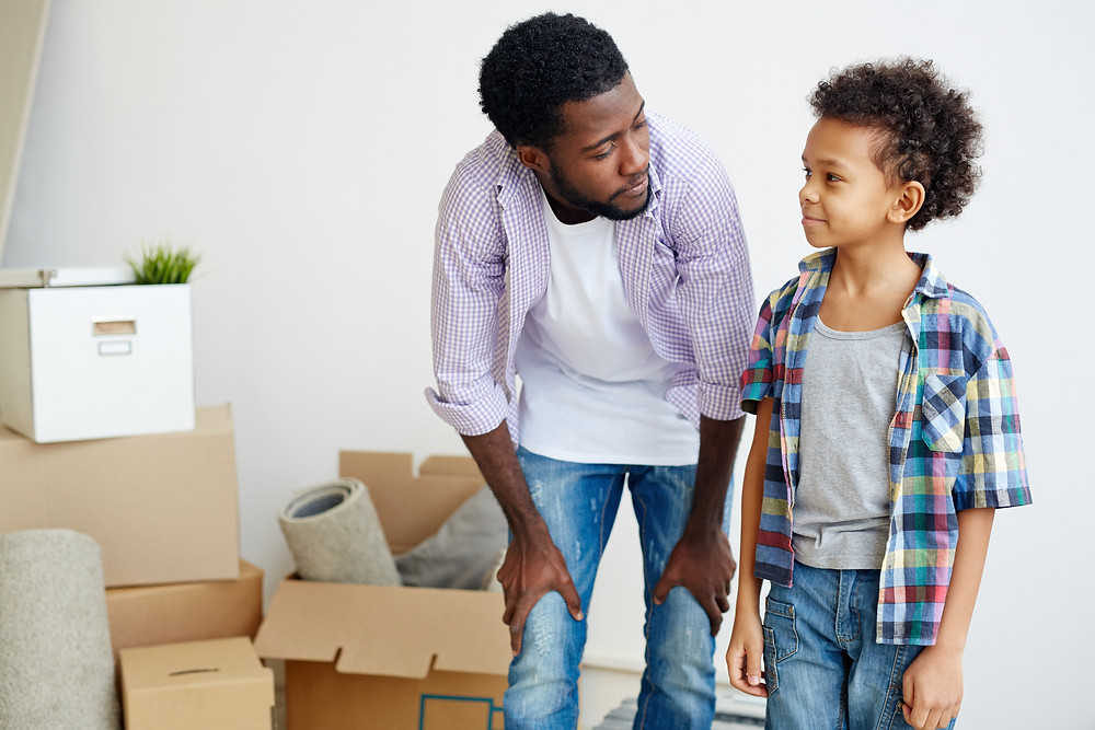 Male Parent and young son packing boxes