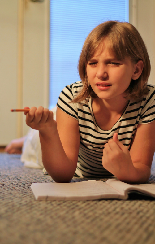 Young girl lays on the ground and looks confused about her homework