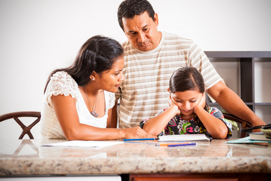Mom and dad helping young child with homework
