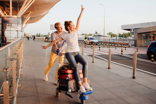 Man pushing girl on top of rolling luggage at an airport with excitement