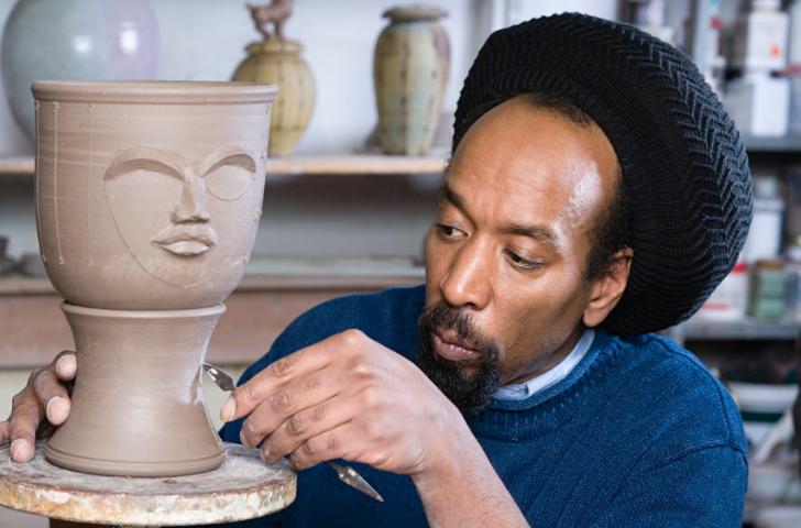 A man sculpting pottery