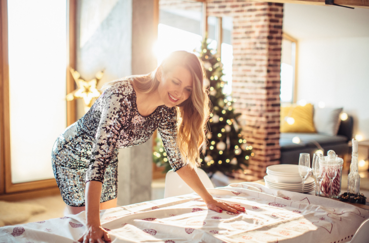 A woman placing a Holiday table cloth on the table