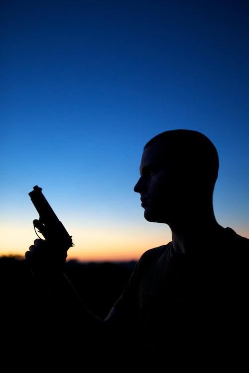 Silhouetted man holding gun