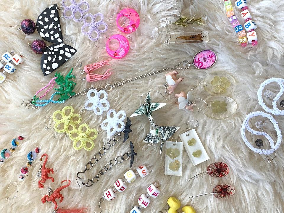 Multicolored earrings on cream colored rug