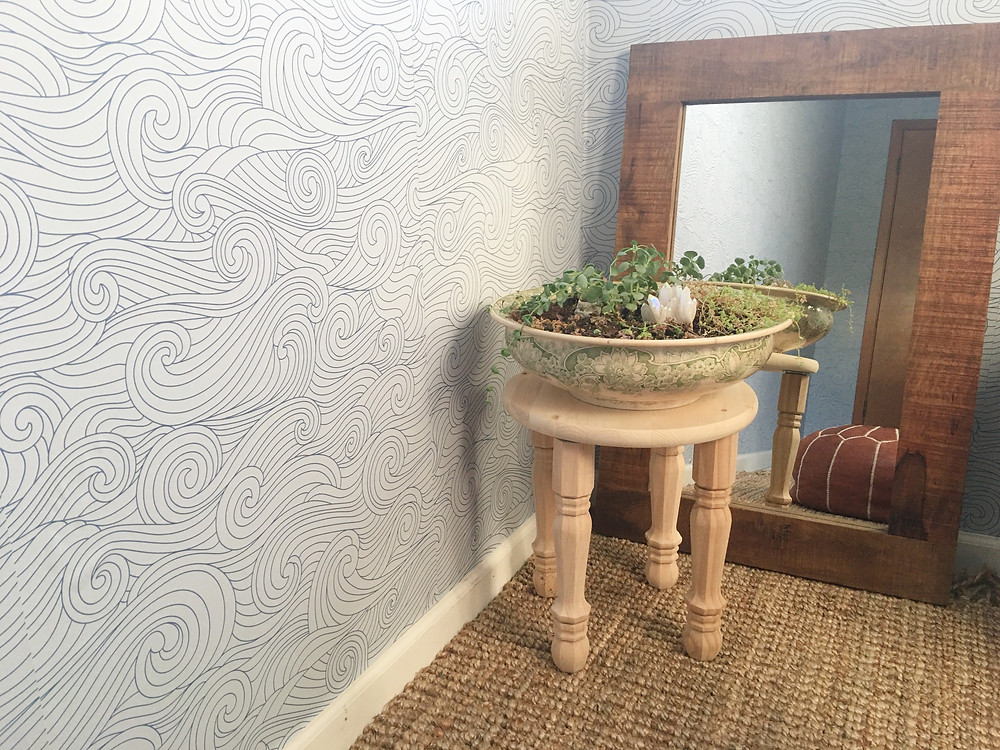 meditation corner with mirror and plants on stand blue wave wallpaper