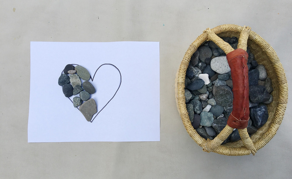 paper with heart outline drawn on it, basket full of rocks, rocks halfway filling in heart outline