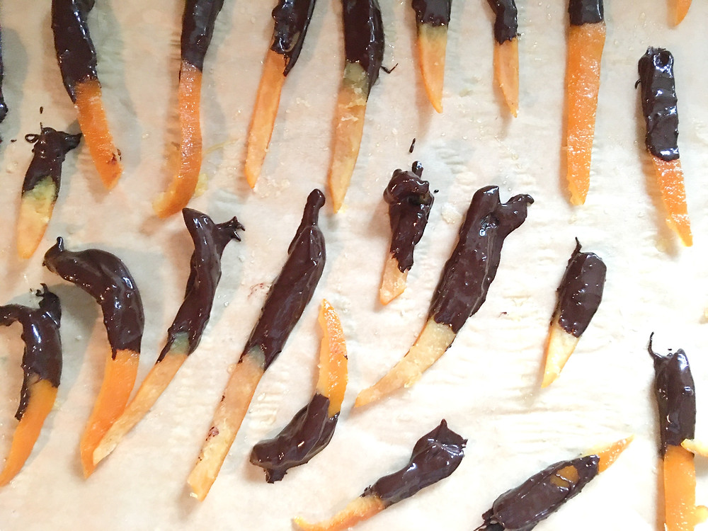 candied orange slices dipped in dark chocolate laying to dry