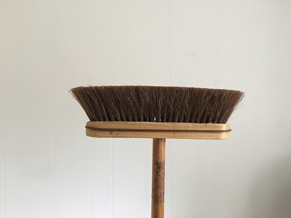 wood handled broom bottom up against a white wall