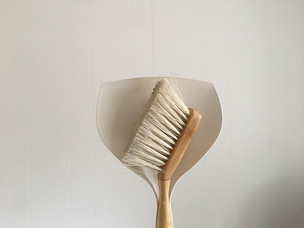handheld broom and dust pan against white wall